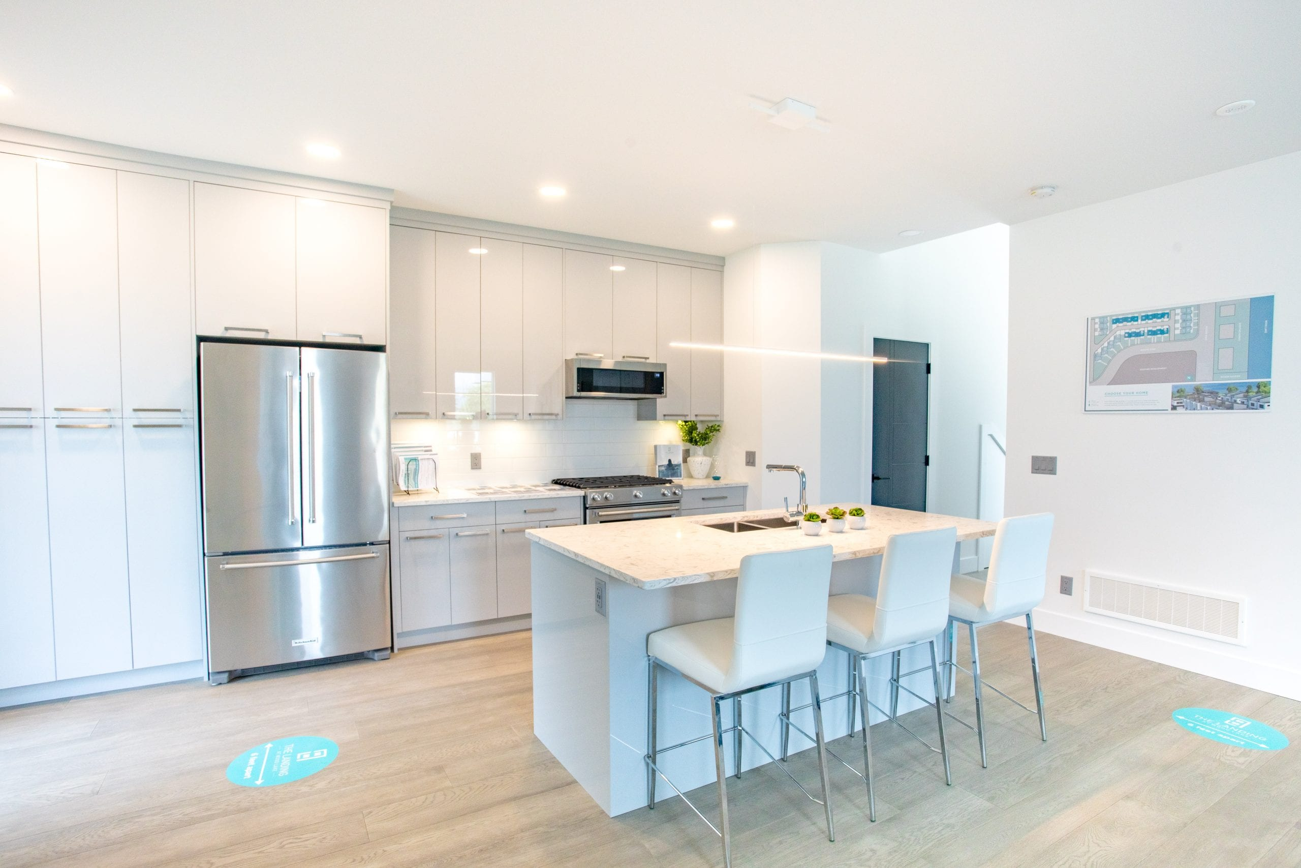Sleek kitchen design with quartz, stainless KitchenAid appliances, high gloss cabinetry and hardwood floors.